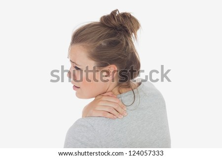 Rear view of young woman suffering from backache over white background
