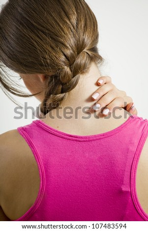 Rear view of young woman suffering from neck pain - stock photo