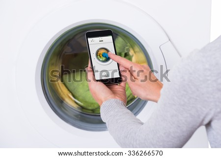 Rear view of young woman using mobile phone to operate washing machine against white background - stock photo
