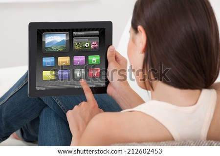 Rear view of young woman using various applications on digital tablet at home