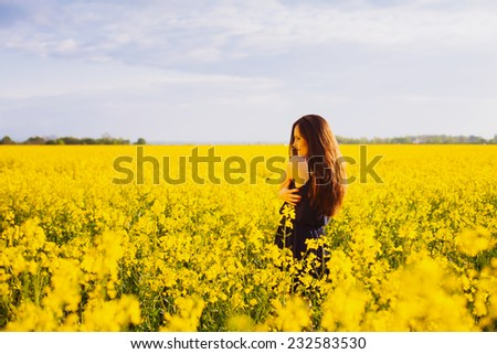 Rear view of young woman with long hair hugging herself on yellow blooming rapeseed field - stock photo