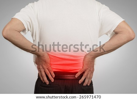 rear view old man grandpa holding his painful lower back colored in red with hands isolated on gray background. Human health problems   - stock photo