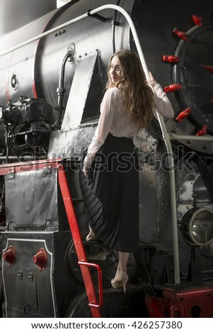 Rear view on beautiful woman in long skirt walking on stairs on old steam locomotive - stock photo