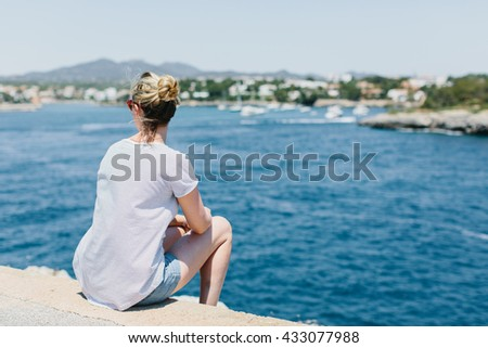 Rear view on woman with tied hair, shorts and gray shirt looking to side while seated on stones at waterfront with copy space