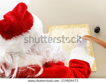 Rear view over Santa Claus' shoulder as he's writing his Christmas list.  Room for your text.