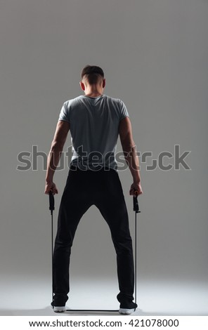 Rear view portrait of a fitness man workout with expander over gray background - stock photo