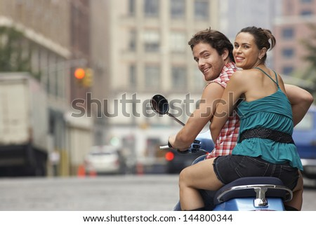 Rear view portrait of a happy couple riding on moped in street - stock photo
