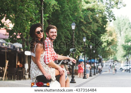 Rear view portrait of a happy couple riding on retro scooter in street on summer day. Beautiful girl and her boyfriend traveling on italian streets. - stock photo
