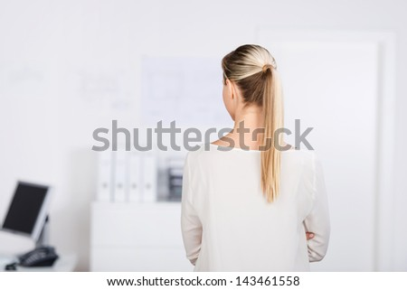 Rear view portrait of a long blond hair woman inside the office