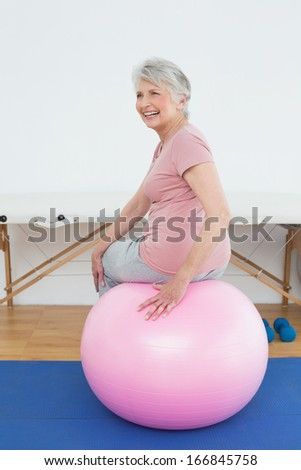 Rear view portrait of a senior woman sitting on yoga ball in the gym at hospital - stock photo