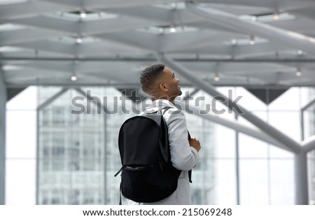 Rear view portrait of a young man smiling with bag at airport