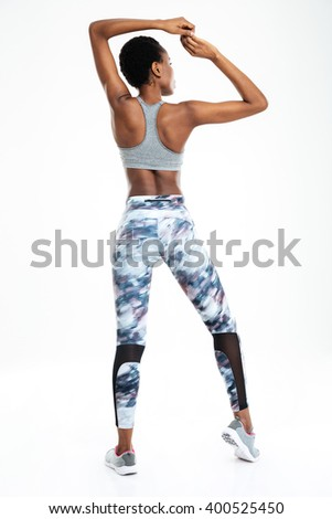 Rear view portrait of afro american woman showing her biceps isolated on a background