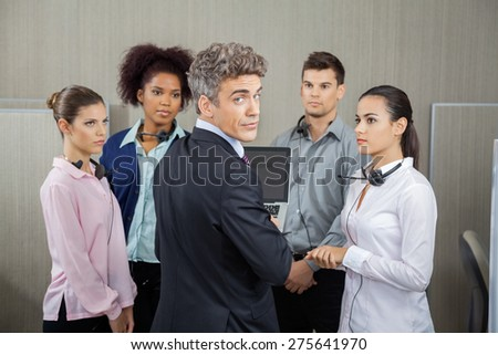 Rear view portrait of confident manager in meeting with employees at call center - stock photo