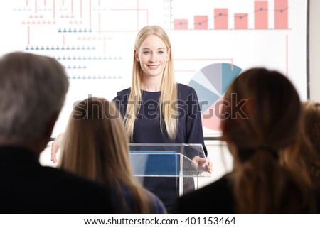 Rear view portrait of large group of business people at a lecture. Focus is on  young blond businesswoman presenting her idea to her colleagues. - stock photo