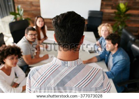 Rear view portrait of man giving business presentation to colleagues in conference room.  Young people meeting in boardroom. - stock photo
