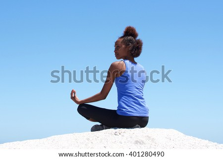 Rear view portrait of young african woman sitting at beach in yoga pose - stock photo