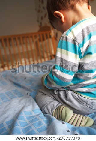 Rear view sad little boy on the bed, natural light - stock photo