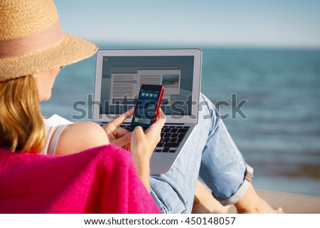 Rear view shot of a woman using her mobile phone and laptop while sitting at beach.