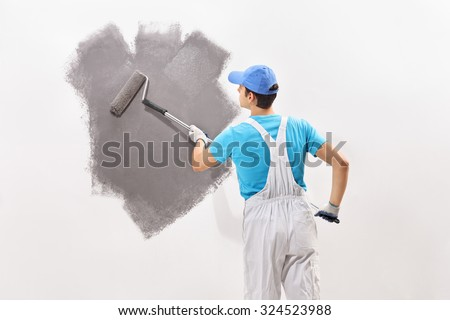 Rear view shot of a young male decorator in white overalls painting a wall with gray color  - stock photo