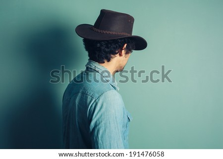 Rear view shot of a young man wearing a cowboy hat