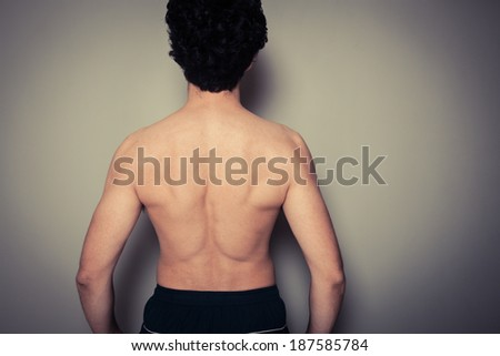 Rear view shot of athletic young man flexing his muscles - stock photo