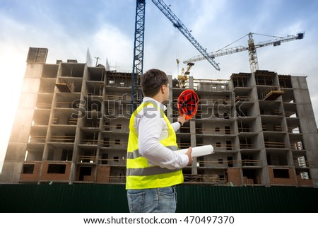 Rear view shot of construction engineer posing on building site at bright sunny sky