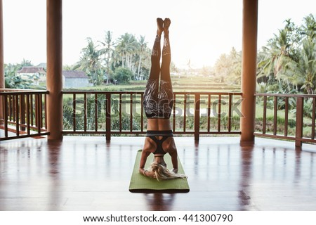 Rear view shot of fitness woman doing the headstand yoga in healthy club. Healthy female doing headstand asana. Sirsasana. - stock photo