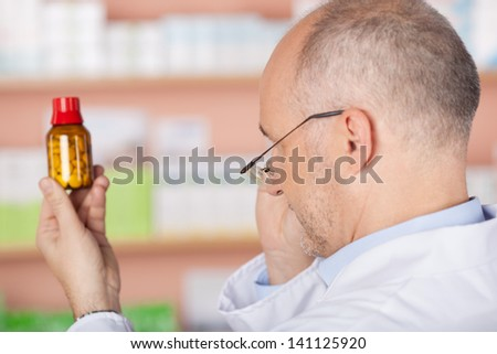 Rear view shot of Pharmacist check the medicine at the drugstore - stock photo