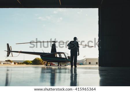 Rear view shot of pilot walking towards helicopter. Pilot and helicopter in a airplane hangar. - stock photo
