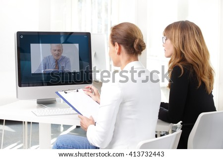 Rear view shot of two businesswoman having video conference with executive senior businessman at office.