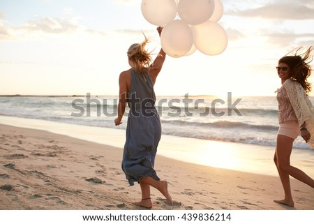 Rear view shot of two young women running along the beach with balloons during sunset. Female friends enjoying a day in the sea shore. - stock photo