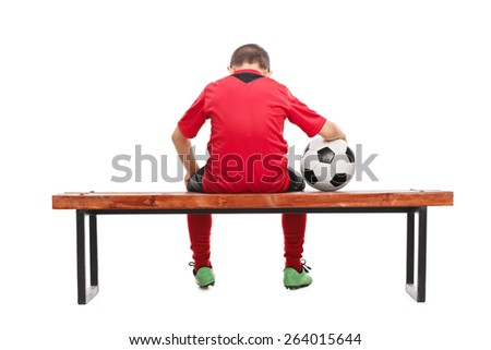 Rear view studio shot of a sad little boy in red soccer jersey seated on a bench and holding a ball isolated on white background - stock photo