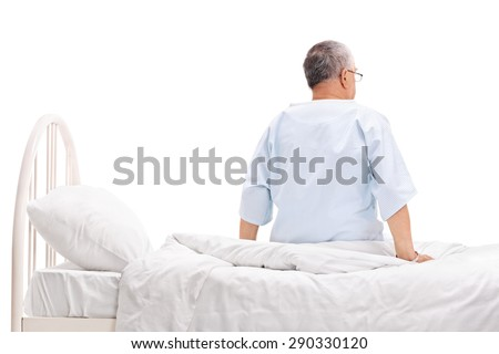 Rear view studio shot of a senior patient in a hospital gown sitting on a hospital bed isolated on white background - stock photo