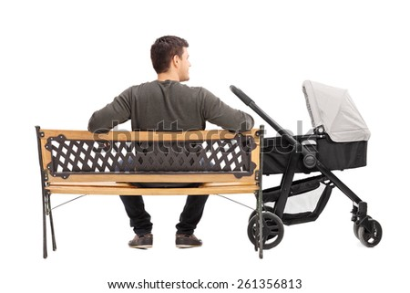 Rear view studio shot of a young father sitting on bench with baby stroller beside him isolated on white background