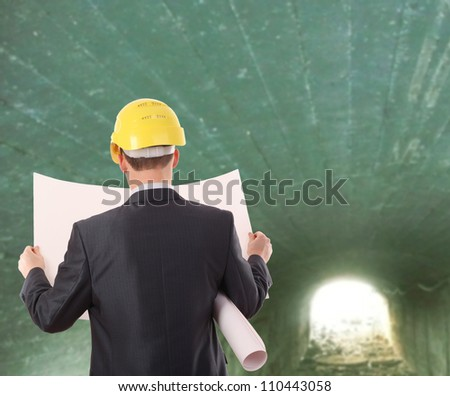 Rear view worker in a tunnel  light at end of tunnel - stock photo