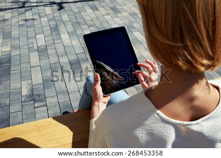 Rear view young businesswoman freelancer working on tablet while sitting on city park bench, female student using touch pad with blank screen outdoors in urban setting, tourist working on tablet  - stock photo