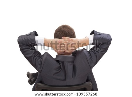 Rear viwe of a relaxed businessman with hands behind his head - stock photo