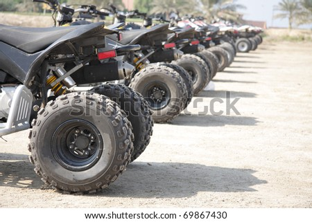 Rear wheel of desert scooter arranged in a row - stock photo