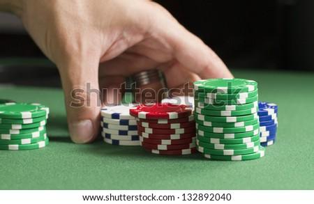 Rearrange Poker Chips a macro shot of a gambler rearranging poker chips on a felt table. shallow depth of field - stock photo