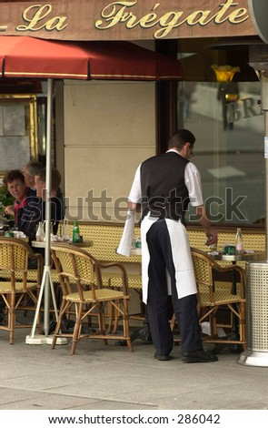 Rearview of a waiter at a table in a street cafe in Paris, France, July 2001 (Keith Levit) - stock photo