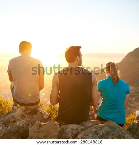 Rearview of three friends sitting quietly on rocks together on a nature hike enjoying the sunrise - stock photo