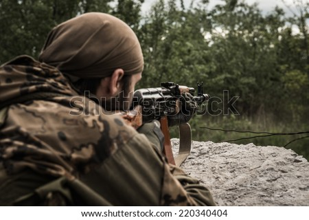 Rebel aiming an assault rifle at target, hidden behind concrete obstacle - rear view - stock photo