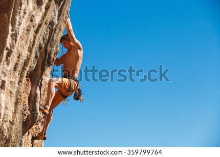 Rebelious rock climber on the wall against the blue sky - bold choice of real men. Dangerous adventure. Turkey, Geyikbayiri - Stock Image, Close-Up