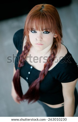 Rebellious teenager girl with red hair very angry view from above - stock photo