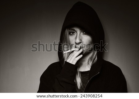 Rebellious teenager in a hooded sweatshirt smoking a cigarette. MANY OTHER PHOTOS FROM THIS SERIES IN MY PORTFOLIO.