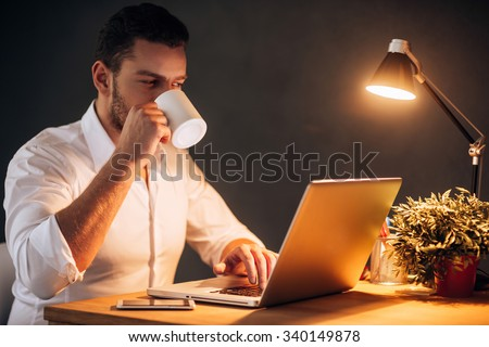 Rebooting his energy to work more. Confident young man drinking coffee while sitting at his working place at night time - stock photo