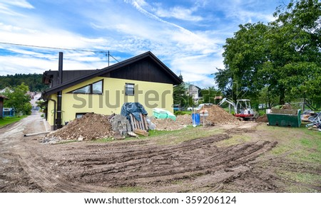 Rebuilding a family house and adding an extension. Setting up a construction site with tools excavator and construction material. - stock photo