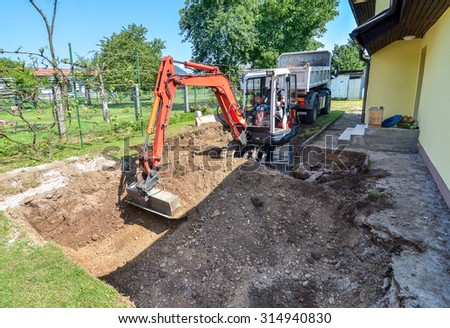 Rebuilding a house and digging dirt with excavator - stock photo