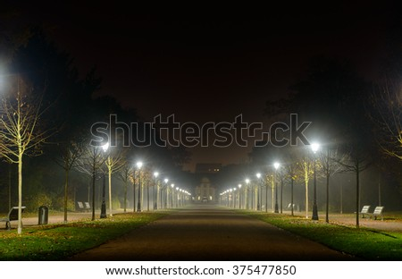 Receding perspective of an illuminated deserted street lit by two rows of street lamps at night disappearing into the distance with copy space above - stock photo