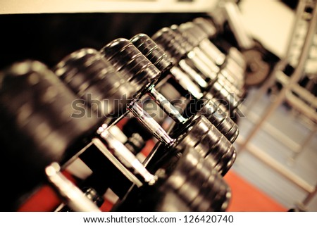 Receding row of weights lined up in a gym waiting for clients with focus to the third and fourth dumbbells in the row - stock photo